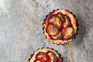 Homemade cake tartlets with plum on old stone background