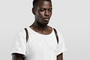 Indoor headshot of good-looking dark-skinned student dressed in white blank T-shirt and leather backpack standing isolated against concrete wall with copy space for your text or advertising content