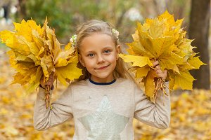 Little girl with a bouquet of autumn