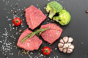 Uncooked beef steaks with vegetables