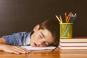 child asleep on the table school