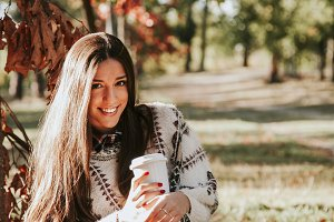 woman in autumn outdoors with cup of coffee