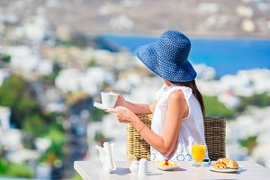 Beautiful elegant lady having breakfast at outdoor cafe with amazing view on Mykonos town. Woman drinking hot coffee on luxury hotel terrace with sea view at resort restaurant.