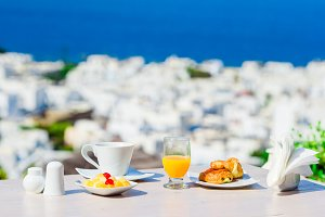 Breakfast served table by the sea. Perfect luxury breakfast table outdoors. Amazing caldera view on Mykonos, Greece, Europe.