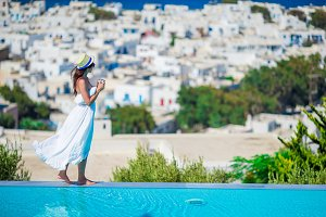Beautiful woman with morning coffee near pool with amazing view on Mykonos, Greece