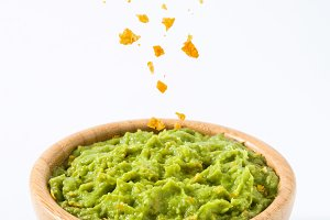 Pouring nachos in bowl of guacamole