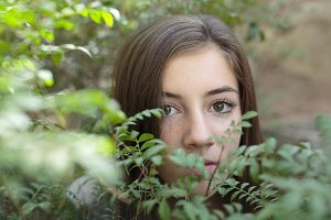 Girl face between green leaves