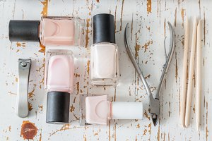 Selection of manicure tools on white wood background