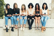 Group of friends using cellphones