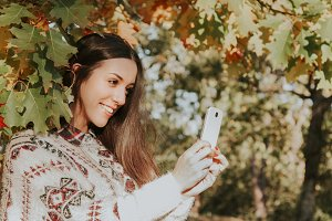 woman in autumn with mobile phone