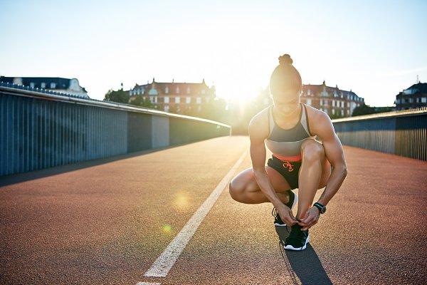 Muscular woman ties her running sho…