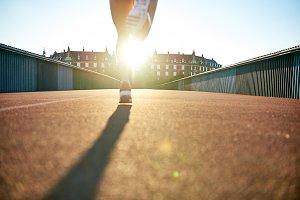 Bare legged athlete runs down empty road