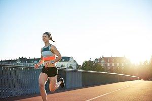 Woman runner sprinting across an urban bridge
