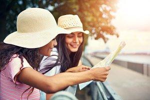 Women wearing floppy summer hats reading a map