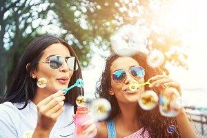 Female friends with sunglasses blow bubbles