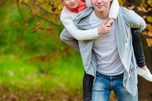 Adorable little girl with father in beautiful autumn park outdoors. Happy family enjoy their weekend outdoors