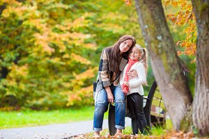 Happy mom with little girl on beautiful autumn day