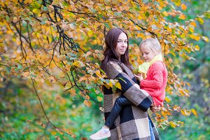 Happy mom with little daughter on beautiful autumn day
