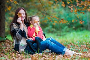 Adorable little girl with mother in autumn park outdoors