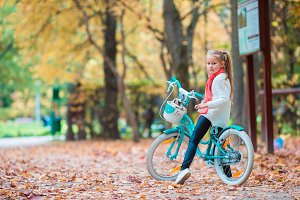 Little girl riding a bike at beautiful autumn day outdoors