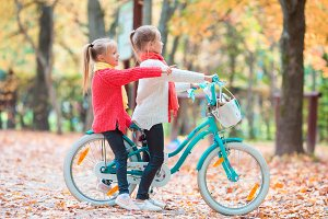 Two adorable girls in park at warm sunny autumn day. Kids on bicycle together