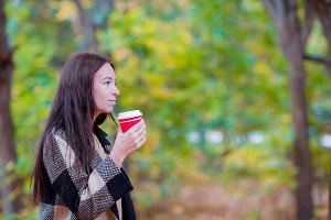 Beautiful woman drinking coffee in autumn park under fall foliage. Coffee to go