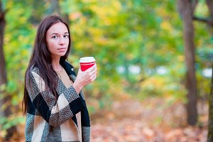 Beautiful woman drinking coffee in autumn park under fall foliage. Coffee to go in her hands