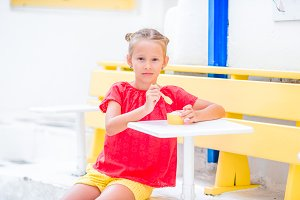 Adorable little girl eating ice-cream outdoors. Cute kid enjoying gelato in Greece