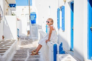 Cute girl in blue dress at street of typical greek traditional village with white walls and colorful doors on Mykonos Island, in Greece