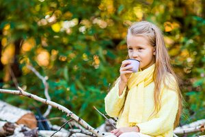 Adorable little girl with hot drink in thermos outdoors at beautiful autumn day