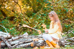 Little cute girl playing with leaves in autumn park outdoors