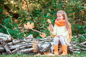 Little girl playing with leaves in autumn park outdoors