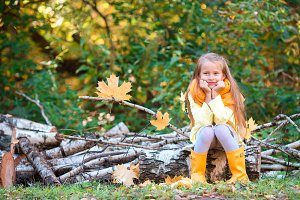 Adorable little girl outdoors at beautiful warm day in autumn park