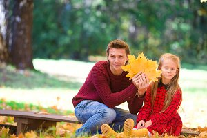 Adorable little girl with father in autumn park outdoors. Happy family together enjoy warm autumn day
