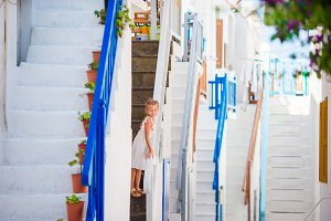 Cute girl in blue dress at street of typical greek traditional village with amazing steps, white walls and colorful doors on Mykonos Island, in Greece