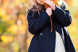 Adorable little girl playing wuth leaves outdoors at beautiful autumn day