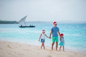 Young father and little girls in Santa hat on the beach