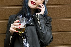 young woman drinking beer with mobile phone