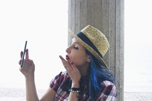 young woman with hat becoming a selfie