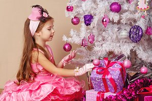 Girl and gift under Christmas tree