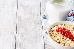 Wooden background with bowl of oats
