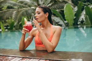 Young woman drinking cocktail