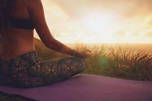 Female sitting in lotus yoga pose