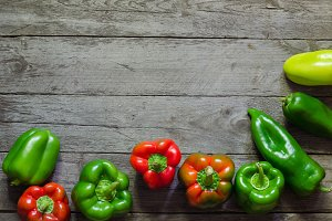 Green and red pepper on wooden background