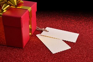 Gift with two tag on red table