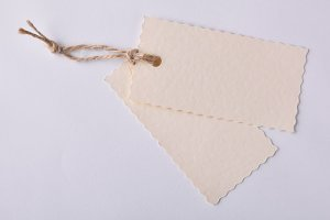 Two beige textured paper tags