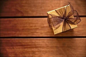 Golden gift box on wood table top
