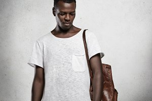 Studio shot of young handsome African student wearing leather backpack and white copy space t-shirt, standing isolated at concrete wall. Black hipster model posing indoors. Advertising concept