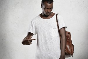 T-shirt design and advertising concept. Indoor portrait of fashionable dark-skinned young male pointing finger at his blank top with copy space for your information, showing something, looking down