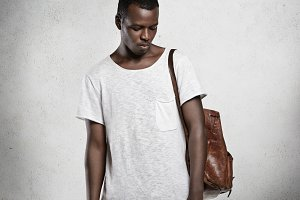 Clothing and advertisement concept. Young stylish African male model with athlete body dressed in white copy space t-shirt, bowing his head with closed eyes, posing against concrete wall in studio